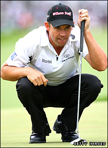 Padraig Harrington squats to read a putt at the first hole