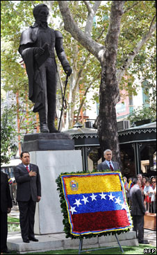 Chavez near a statue of Bolivar