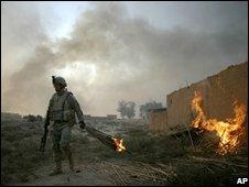 A US soldiers burns deserted buildings near Balad Ruz, Diyala province