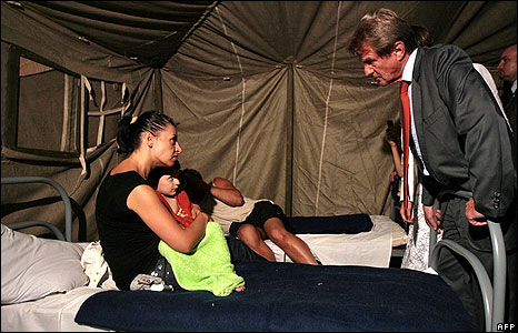 French Foreign Minister Bernard Kouchner talks to a refugee and her child in a camp in Alagir, North Ossetia