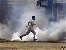 Kashmiri Muslim protester runs for cover as tear gas shell explode near them during a march in Srinagar 11 August