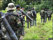 Philippine police patrol the village of Takepan, North Cotabato province, on Tuesday, after it was vacated by rebels