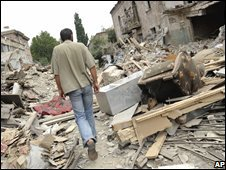 A Georgian man walks by his destroyed apartment building in Gori, Georgia, 12 August 2008