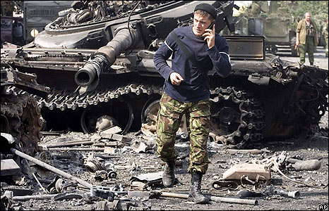 "A man identified as an ""Ossetian soldier"" makes a phone call beside a wrecked tank in Tskhinvali on 11 August"