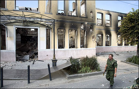 A Russian officer passes a ruined administrative building in Tskhinvali on 11 August