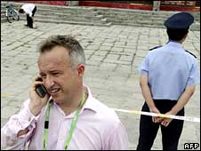 John Ray, ITN's China correspondent, speaks on his phone after being briefly detained by Chinese police near the Olympic National Stadium in Beijing on Wednesday