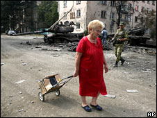 A woman with her belongings in a street in Tskhinvali