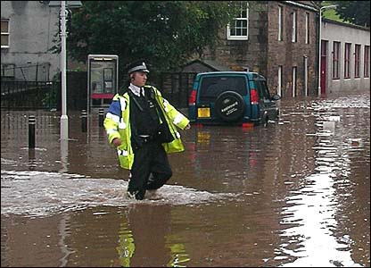 Policeman wading through a flooded street