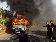 The car of cameraman Fadel Shana burns after it is hit by a shell, 16 Apr 2008