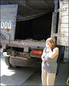 A woman, Marina, stands next to the truck in which she sleeps