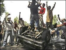 Kashmiri Muslims atop a burnt-out police car in Srinagar on 14 August 2008