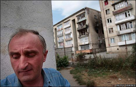Man near burned out apartments
