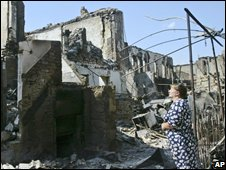 A woman looks at ruined buildings in Tskhinvali