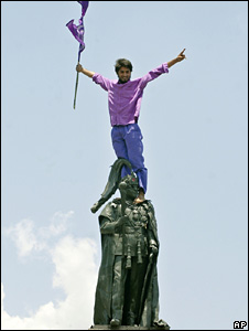A demonstrator urging the king to leave palace climbs atop a statue of King Birendra, May 2008