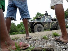 Local villagers watch army troops in North Cotabato on 12 August 2008