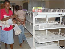 Shoppers walk past empty shelves in Harare. File photo