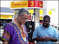 Rocky Twyman, izq., dirige rezos frente a una gasolinera.