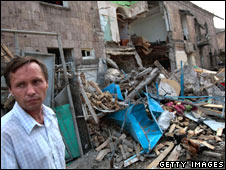 A Georgian man stands near where a Russian bomb destroyed a Georgian block of flats.
