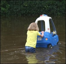 Child pushing car through flood at Maze - Pic David McCleland
