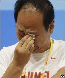 Coach Sun Haiping cries during a press conference after the withdrawal