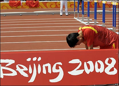Liu Xiang crouches next to a billboard