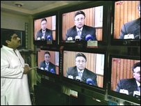 "A Pakistani seller listens the address of country""s President Pervez Musharraf in Islamabad"