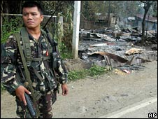 A soldier stands outside a burned-down house in Lanao del Norte on 18 August 2008