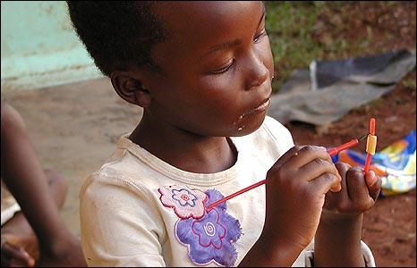 Girl painting with a purple flower on her top in Kisii, Kenya [Photo: David Steggall]