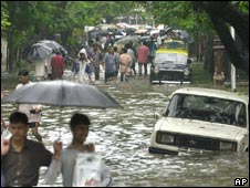 People wade through a flooded street during heavy rains in Mumbai, India