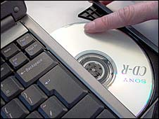 A CD-rom being placed in a laptop