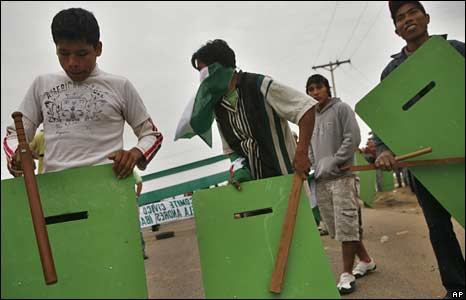 Protesters hold makeshift shields and wooden sticks as they stand guard in front of a road blockade in Santa Cruz, eastern Bolivia, Tuesday 19 August 2008