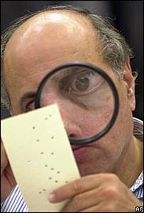 Un trabajador electoral examina una papeleta en las elecciones de 2000