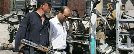 A policeman and a bomb disposal expert at the site of a bomb attack in Bouira, 20 August 2008