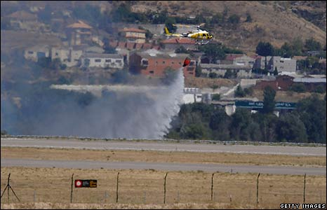 A helicopter dumps water at the site of the crash
