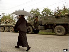A woman walks past a convoy of Russian troops in Georgia. Photo: 20 August 2008