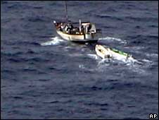 Suspected pirates flee the scene near the Gem of Kilakari, in the Gulf of Aden on 8 August 2008 - chased off by the US Navy