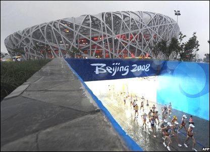 Olympic athletes pass in front of Beijing's National Stadium