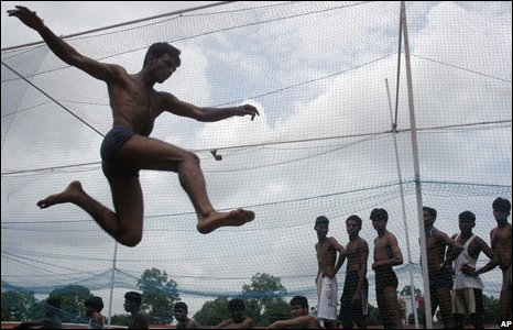 A youth jumps as others look on during an Indian Army recruitment rally in Ahmadabad, India