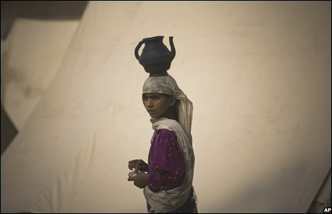 A Pakistani girl from the Bajaur tribal region carries a pot with water on her head at a relief camp at a school compound near Peshawar, Pakistan