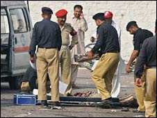 Pakistani security officials examine the site of the suicide bombing in Wah