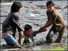 Two youths pull a man to higher ground after the tsunami strike in Banda Aceh, Indonesia, 26 December, 2004