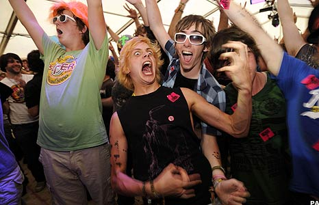 Festival-goers playing air guitar