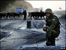 "A Russian soldier, his helmet marked ""Peacekeeping Forces"", watches combat troops pull out of Georgia on 22 August"