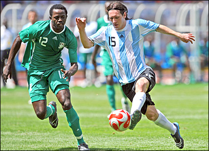 Lionel Messi holds off the challenge of Nigeria's Ebenezer Ajilore