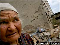 Georgian woman walks past a bombed building, 23 August 2008 in Gori, Georgia