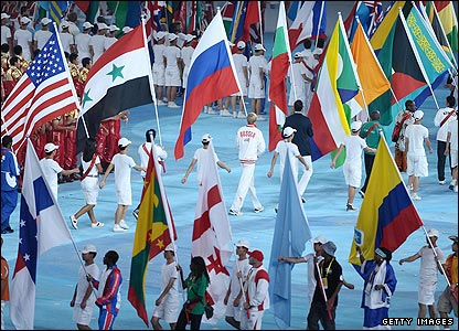 Thousands of Olympians flood into the stadium behind their national flags