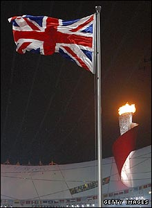 The Union Flag is hoisted in the Bird's Nest as the flame still burns