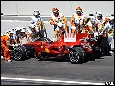 Marshals push away Kimi Raikkonen's Ferrari following its retirement with engine failure