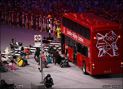 A London bus emerges and travels around the stadium before pulling up at a bus stop