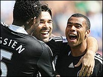 Michael Essien (left) and Ashley Cole (right) congratulate Deco after the midfielder scored from a free-kick at Wigan